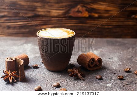 Capuccino in handmade clay cup with cinnamon and anise spices