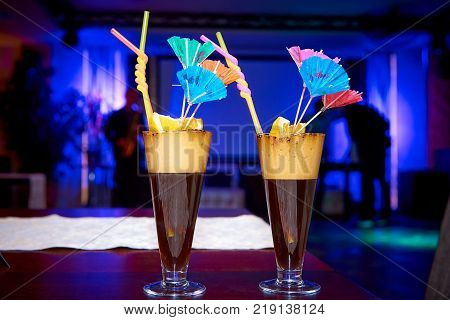 Bright exotic cocktails decorated with lemon straws and umbrellas on the table in the restaurant