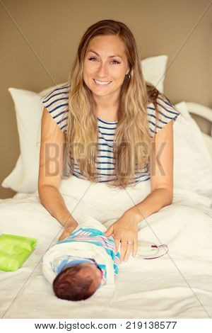 Attractive young mother sitting on a hospital bed and caring for her new young newborn son. So happy with the birth of her new healthy baby