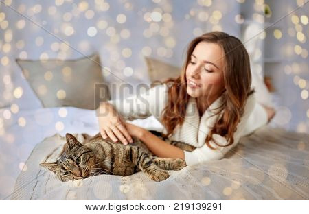 pets, comfort, christmas, winter and people concept - happy young woman with cat lying in bed at home