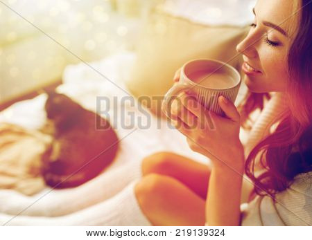winter, coziness, leisure and people concept - close up of happy young woman with cup of coffee or cocoa drink and cat in bed at home