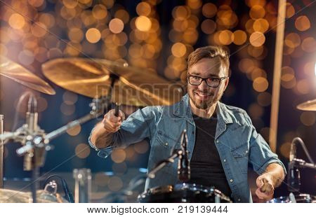 music, people, musical instruments and entertainment concept - male musician or drummer playing drums and cymbals at concert or studio over holidays lights background