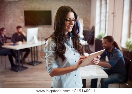 Portrait of young beautiful female designer using tablet in office