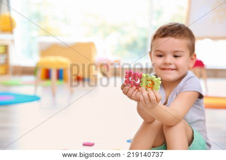 Cute little boy playing with math puzzle at home