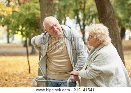 Elderly woman and her husband with walking frame in autumn park