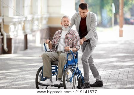 Young caregiver walking with senior man, outdoors