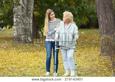 Young woman and her elderly grandmother with walking frame in autumn park