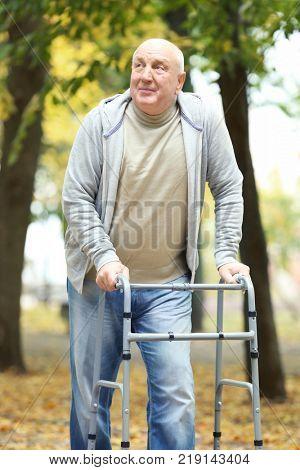 Elderly man with walking frame in autumn park