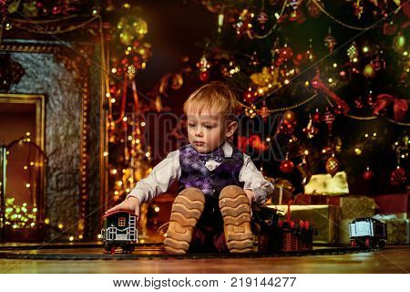 Cute three-year-old boy playing with a toy railway near the Christmas tree. Christmas night. Christmas decoration.