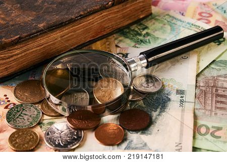 Old antigue vintage book, collection of paper money banknote bills, ancient coins and magnifying glass, close-up. Purchase, sale and pledge antiques, pawnshop.