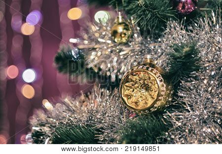 Unusual hemisphere on a Christmas tree in shiny tinsel garland with on blurred background