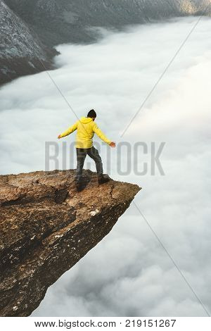 Man tourist on Trolltunga rocky cliff edge mountains Travel Lifestyle adventure emotional concept wanderlust vacations in Norway outdoor above clouds poster