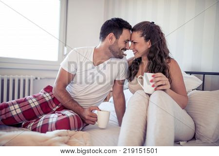 Couple in bed holding cups.Happy young couple sitting on the bed and drinking coffee in the morning.
