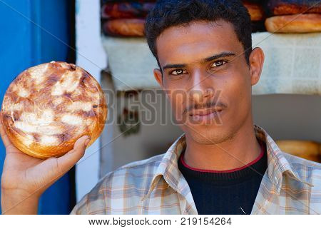 SANAA, YEMEN - SEPTEMBER 16, 2006: Unidentified young man sells traditional burned goat cheese at the market in Sanaa, Yemen.
