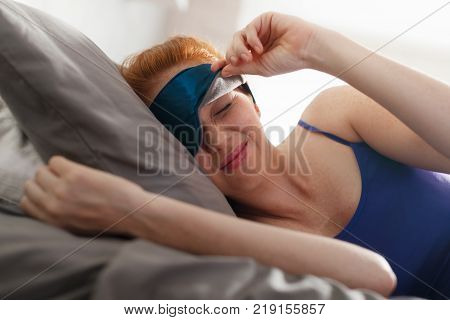 Young redhead woman resting in bed in the morning until late. She sleeps using sleeping mask to cover her eyes from daylight and wakes up irritated.