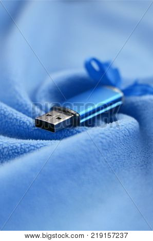 Brilliant blue usb flash memory card with a blue bow lies on a blanket of soft and furry light blue fleece fabric with a lot of relief folds. Memory storage device in women's design