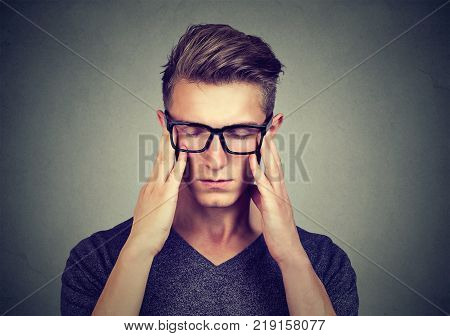 Closeup portrait of a sad young man with worried stressed face expression looking down