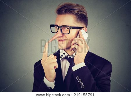 young sly man with long nose talking on mobile phone isolated on gray wall background. Liar concept. Human emotion feelings