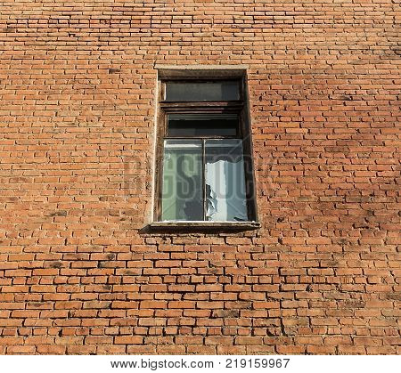 Old window in an old brick house. Old architecture. Old window. Grunge architecture. Grunge window. Brick wall. Firebrick.