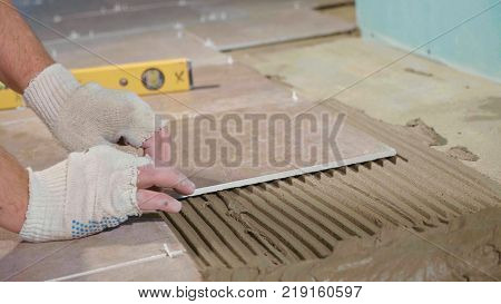Professional worker laying tiles on floor at construction site close-up. Builder puts concrete on tile.