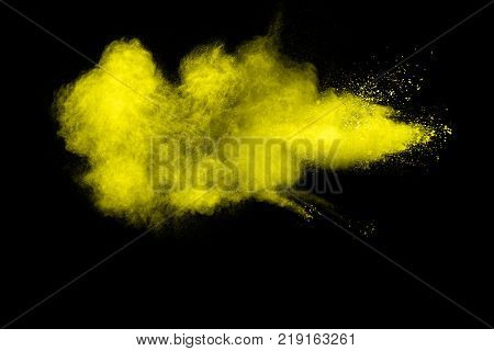 abstract yellow dust explosion on black background. abstract yellow powder splatter on black background. Freeze motion of yellow powder splash.