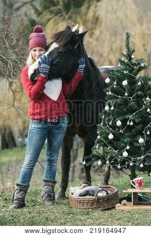 Woman and her horse having fun outdoors. Christmas mood. Happy girl enjoys Christmas magic outdoor.