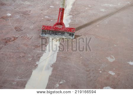 Manual worker scraping excess part of cement using broom at construction site.