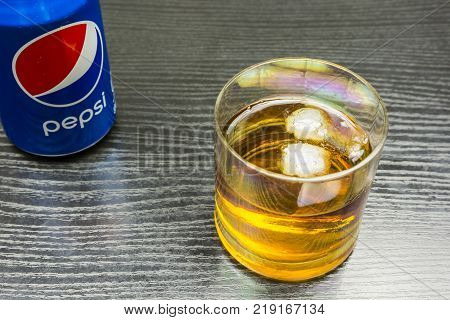 Niedomice Poland - December 20 2017: A glass of whiskey with ice and a can of Pepsi-cola on a wooden table.
