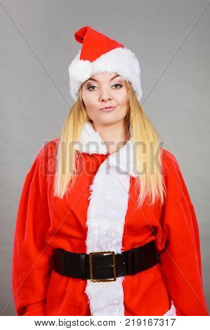 Xmas seasonal clothing winter christmas concept. Dissatisfied annoyed woman wearing Santa Claus helper costume