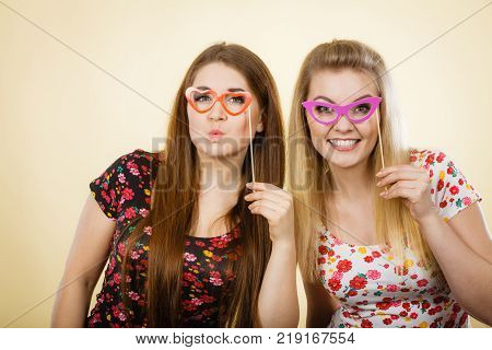 Two happy women holding fake eyeglasses on stick having fun wearing tshirts with flower pattern. Photo and carnival funny accessories concept.