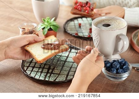 Woman spreading chocolate paste on toast at table, closeup