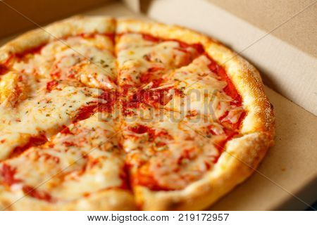 Pizza in a cardboard box against. Space for text. View from above. Pizza delivery. Pizza menu.