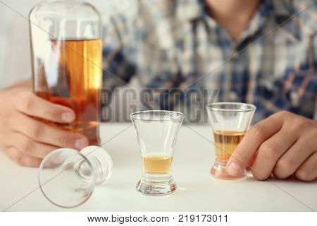 Man with bottle and glasses of brandy indoors. Alcohol dependence concept