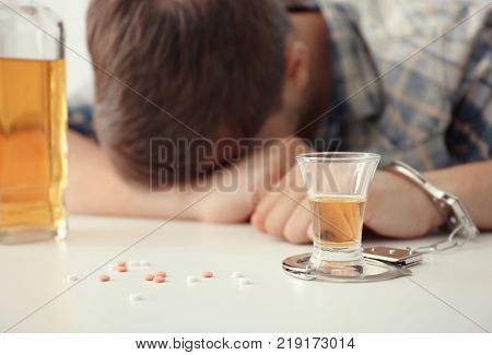 Drunk man in handcuffs sitting at table with bottle and glass of brandy. Alcohol dependence concept