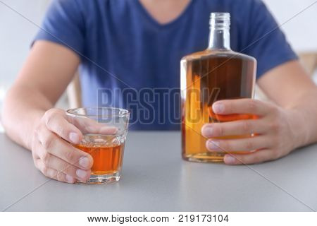 Man with glass and bottle of whiskey indoors. Alcohol dependence concept