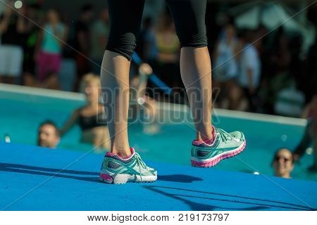 Close-up of Instructor Legs at Swimming Pool Edge- Aqua Aerobics Workout.