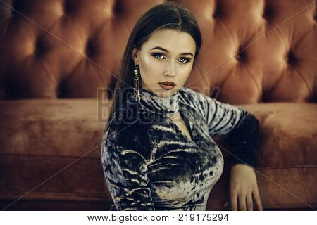 Beautiful woman wearing luxury evening dress and earrings with makeup posing on red sofa