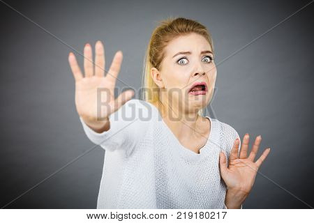 Scared woman gesturing stop gesture with hands seeing something unpleasant or scary.