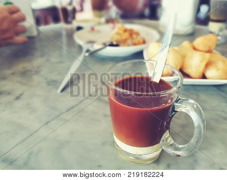 A glass of Thai traditional drink on blurred background - side view; Multi-layered of hot coffee and sweetened condensed milk; Selective focused; vintage style color; Copy-space on the left