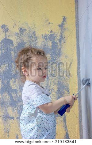 Little kid girl paints wall by paint roller.