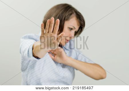 Mid adult emotional woman showing stop sign. Prohibition symbol