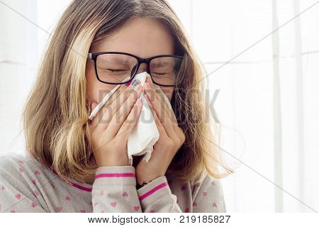 Sick teen girl with handkerchief at the home
