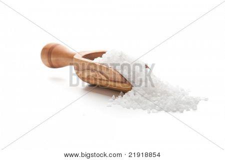 Sea salt poured from wooden scoop