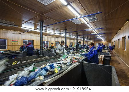GRODNO BELARUS - OCTOBER 16 2017: Separate garbage collection. Recycling and storage of waste for further disposal. Workers sorting material to be processed in a modern waste recycling plant