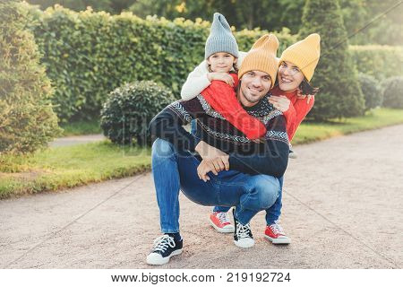 Beautiful female little girl embrace their handsome father and husband have good relationship have active lifestyle pose against green trees. Family have walk together embrace each other