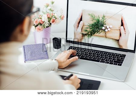 woman retouching on computer laptop using digital tablet and stylus pen