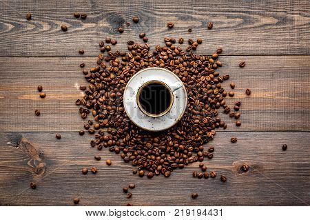 Cup of freshly brewed full-bodied coffee on dark wooden table top view. Coffee background