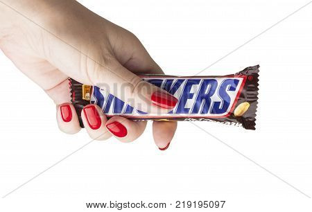 CHISINAU, MOLDOVA - December 21, 2017: Hand holding a Snickers chocolate bar. Snickers bars are produced by Mars Incorporated. Snickers was created by Franklin Clarence Mars in 1930