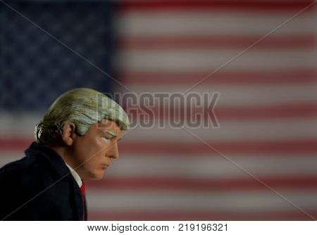 Caricature of United States President Donald Trump looking down in front of a United States flag