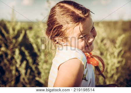 Cute shy plumpy girl in summer rural field in countryside during summer holidays symbolizing happy carefree childhood